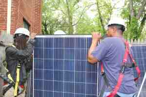 Workers check solar panels at a home in Northeast Washington, May 3, 2016. (Xiumei Dong/MNS) - See more at: http://dc.medill.northwestern.edu/blog/2016/05/10/turning-low-income-neighborhoods-on-to-solar-power/#sthash.pPZMk88y.dpuf